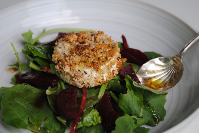Cobnut goats cheese on salad with dressing spoon