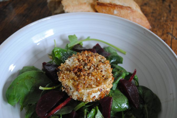 Kent cobnut covered goats cheese on salad in bowl