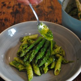 Drizzling kent cobnut pesto over pasta and asparagus