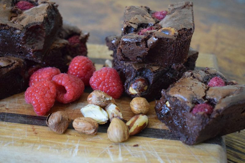 Scrumptious raspberry and cobnut brownies on wooden board surrounded by cobnuts